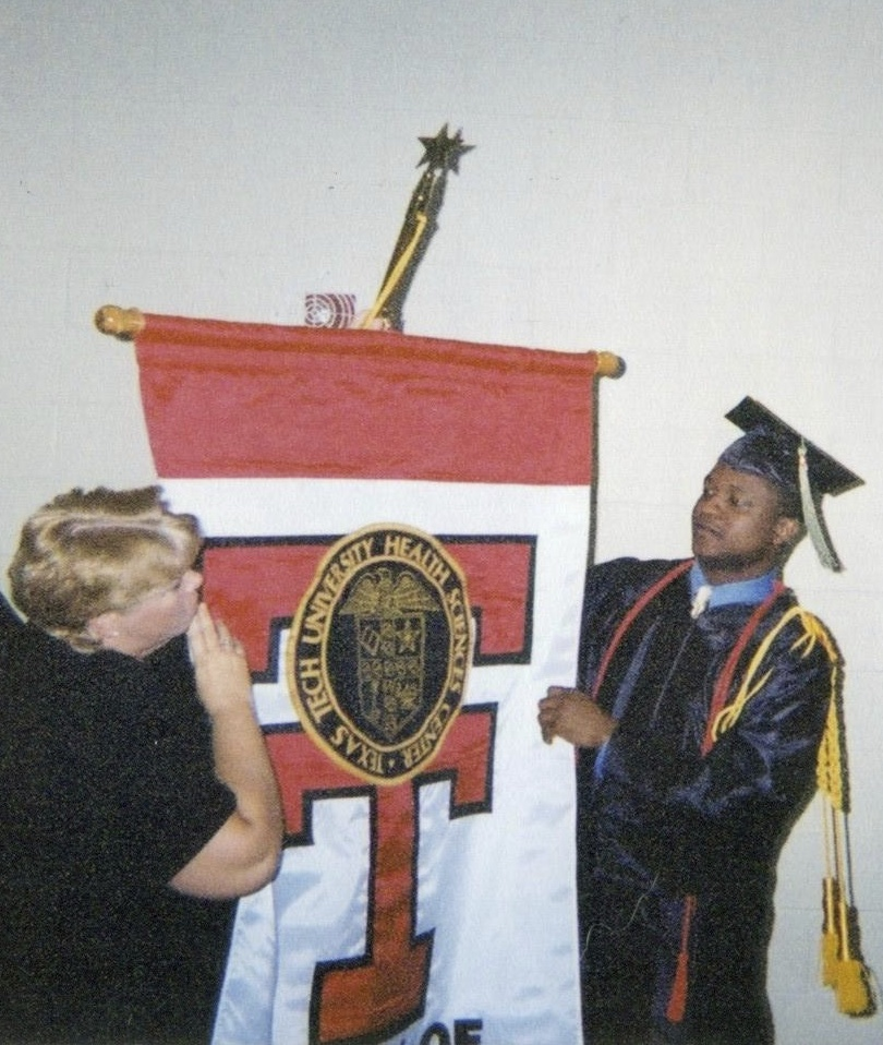 Chapter6 Jenner Bonner assisting me as I get ready to lead the Texas Tech Health Sciences Center graduating class 0f 2002 as the flag bearer